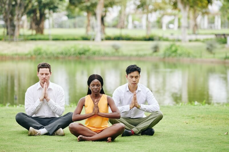 three people meditating sitting on grass to represent your business your body your brain speaking topic